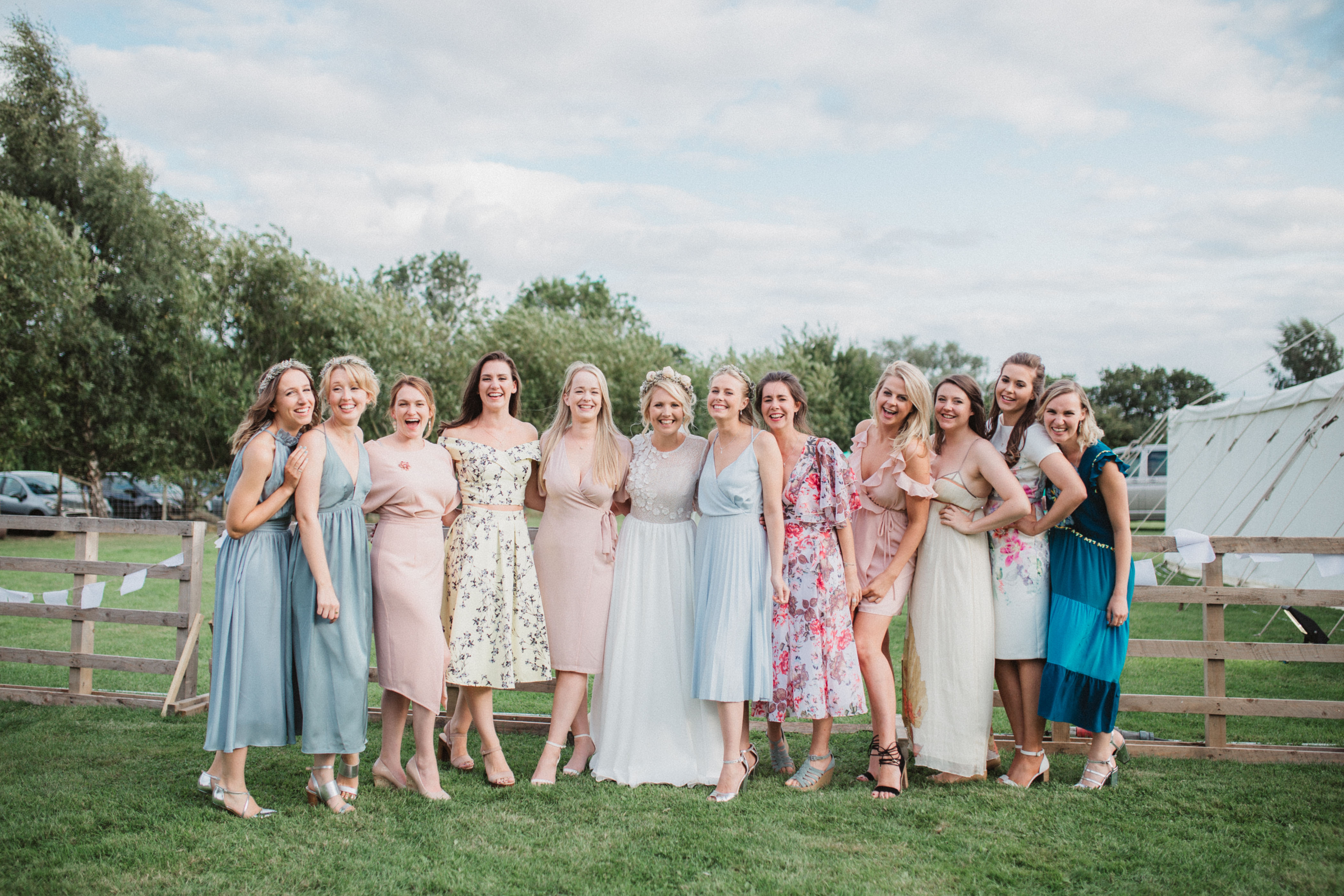 laughing bride and bridesmaids together at marquee wedding in woodbridge, suffolk