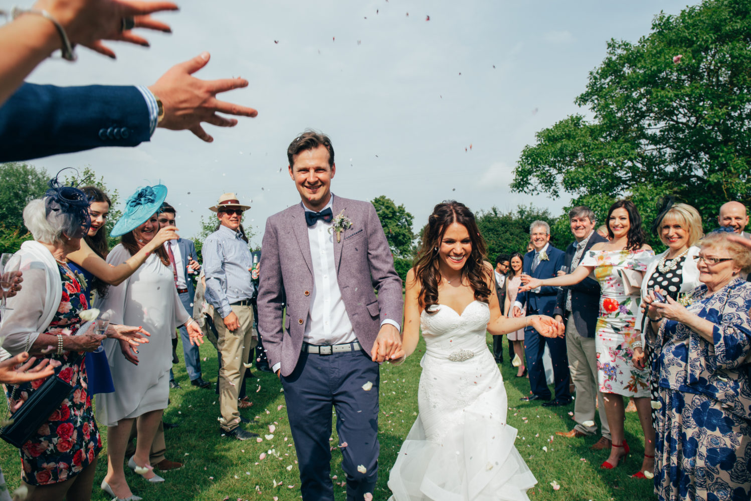 bride and groom laughing during confetti throw at dove barn