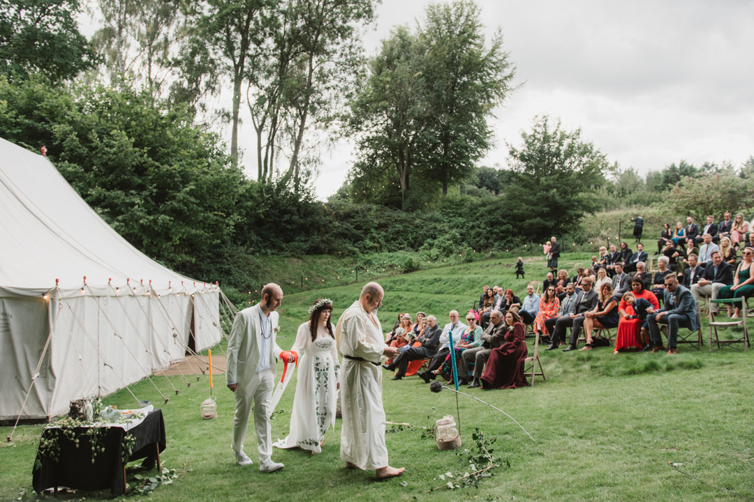 bride and groom dressed in white for pagan hand fasting ceremony outdoors