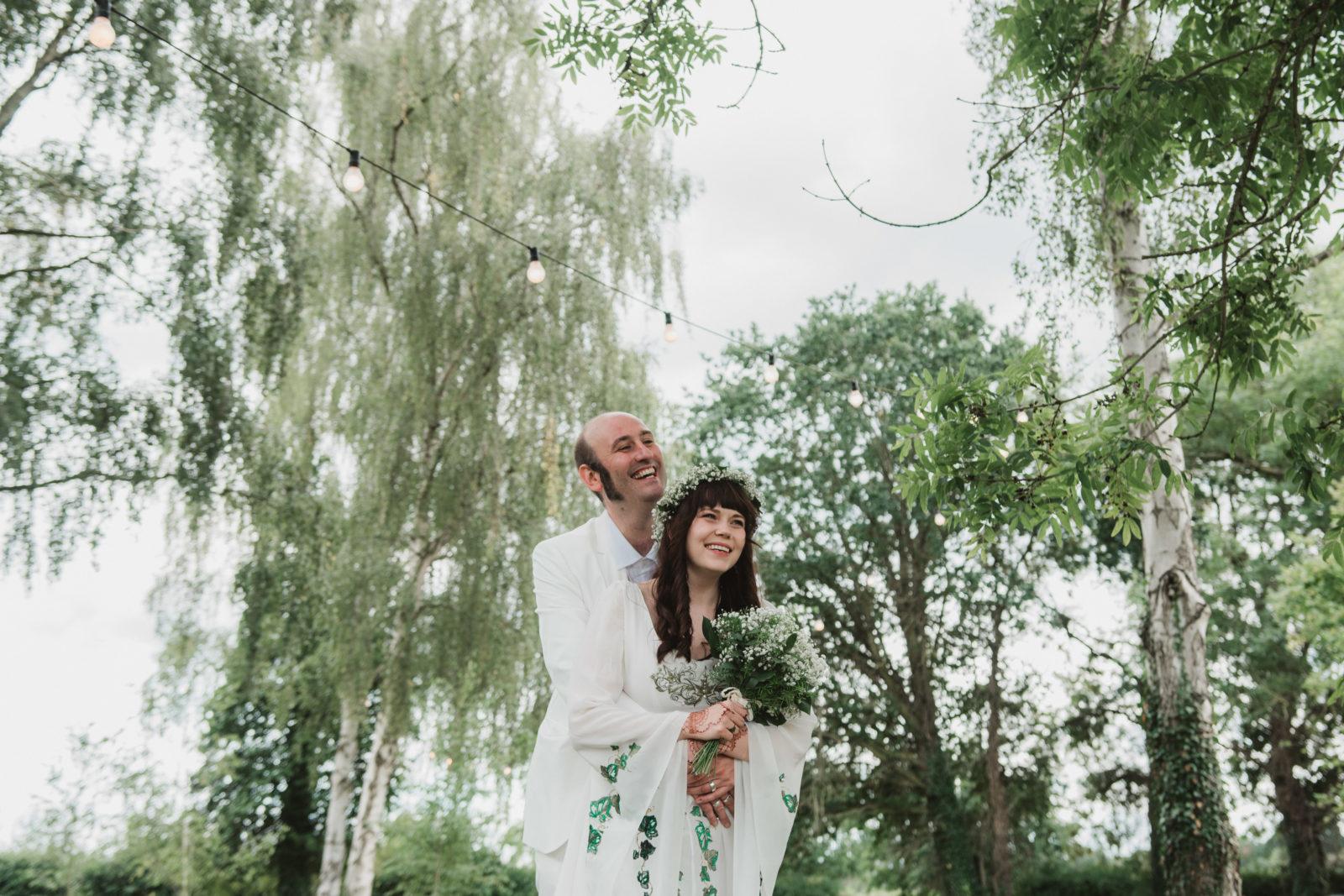 bride and groom hugging at unique suffolk wedding venue upthorpe wood