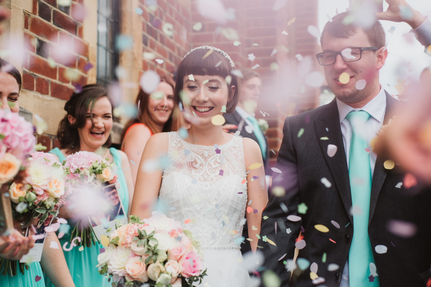 colourful giant confetti throwing over bride and groom