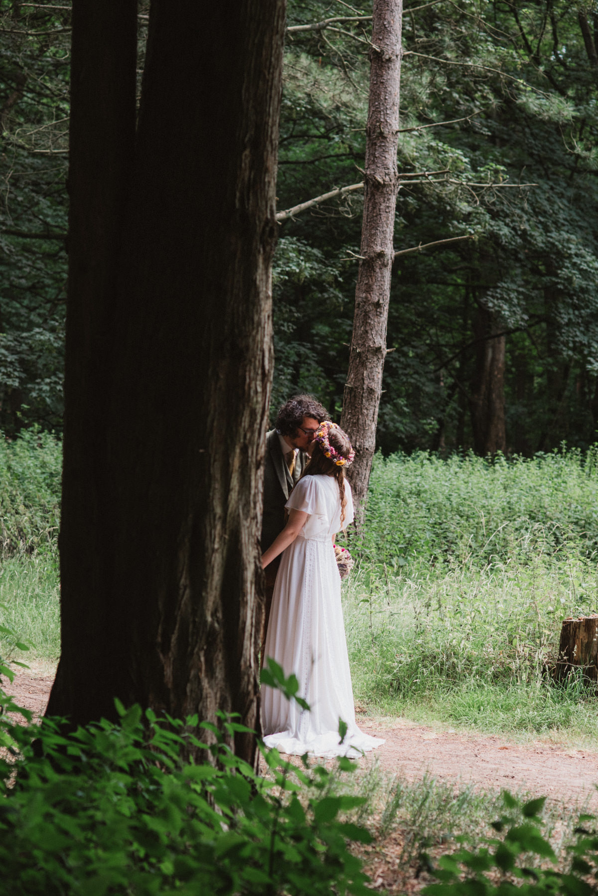 Bride and groom kiss behind tree at Oak Lodge Thetford Forest Wedding Photography