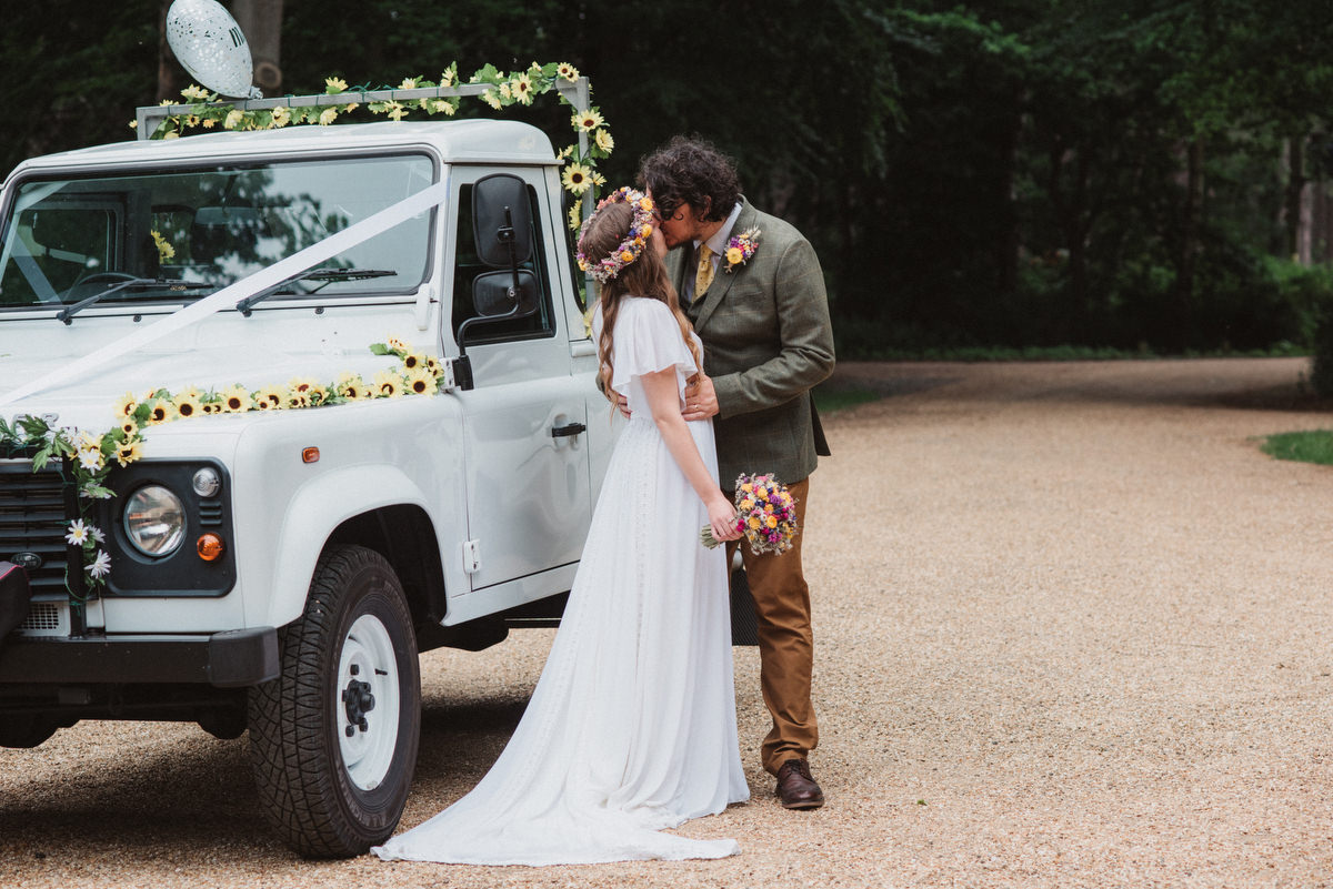 Bride and groom kiss by land rover wedding car Oak Lodge Thetford Forest Wedding Photography
