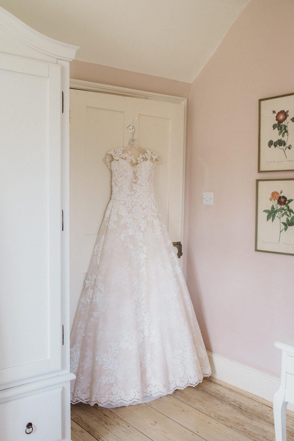 wedding dress hanging at bridal prep on a pink wall at the farmhouse at HAUGHLEY PARK BARN WEDDING PHOTOGRAPHY