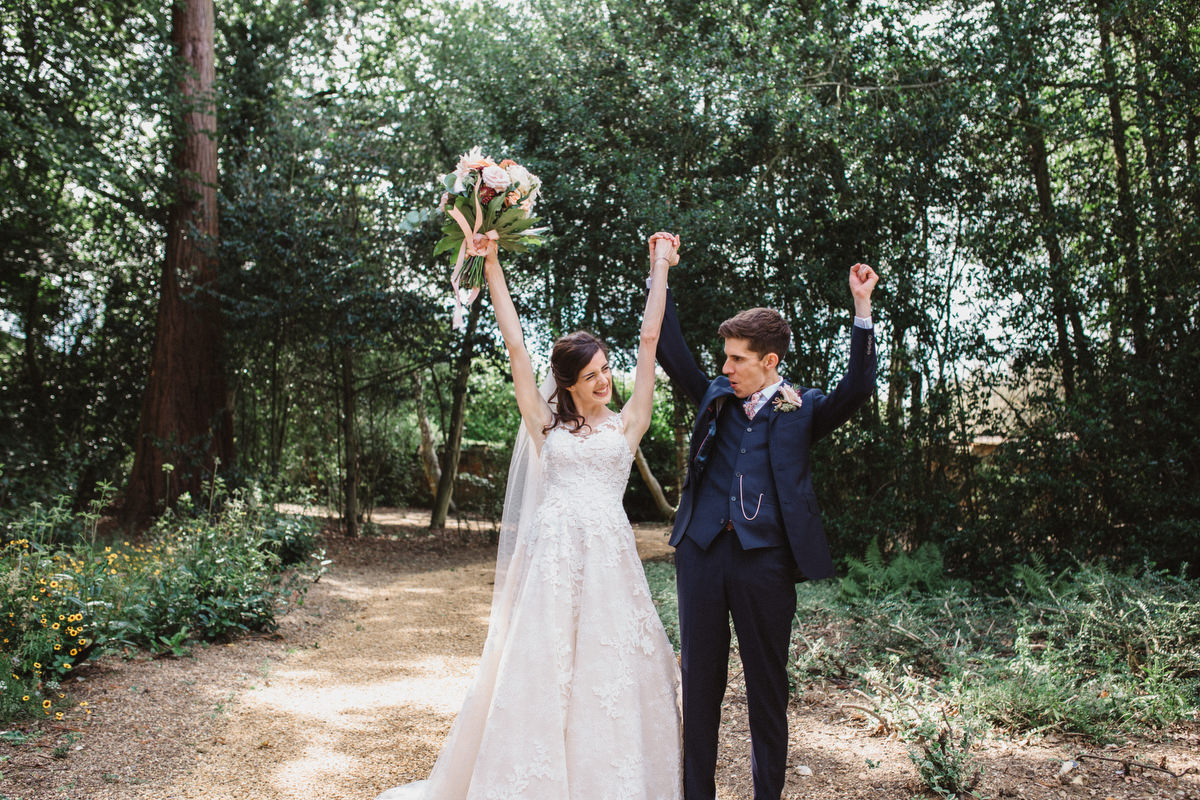 bride and groom cheering outside HAUGHLEY PARK BARN WEDDING PHOTOGRAPHY