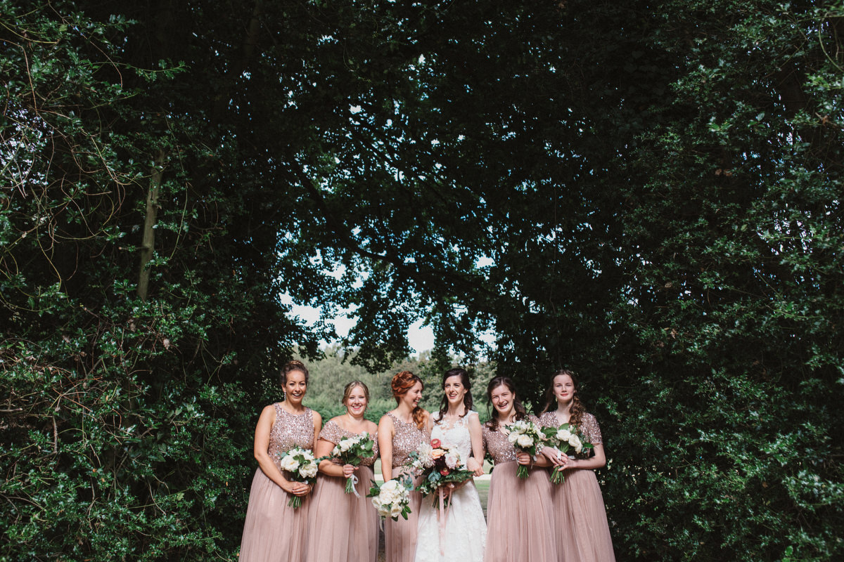 pink bridesmaids laughing and smiling outside at HAUGHLEY PARK BARN WEDDING PHOTOGRAPHY