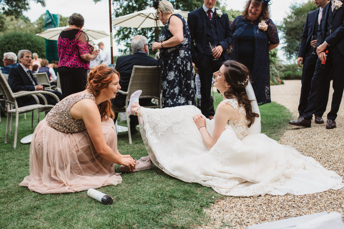 bridesmaid helping bride with shoe change at HAUGHLEY PARK BARN WEDDING PHOTOGRAPHY
