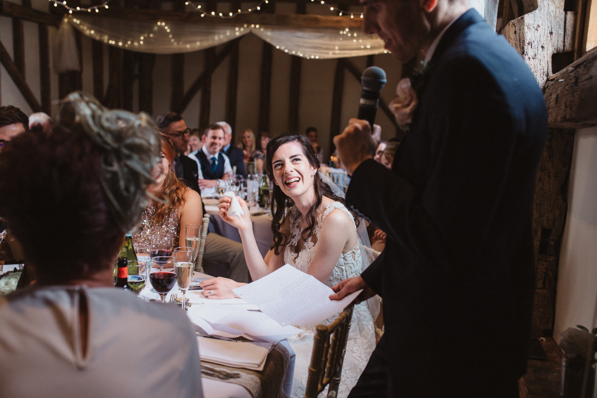 bride watching groom during his speech at HAUGHLEY PARK BARN WEDDING PHOTOGRAPHY