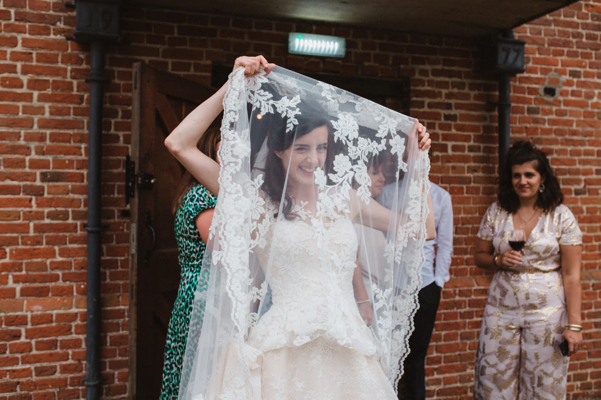 bride hiding under lace on wedding dress at HAUGHLEY PARK BARN WEDDING PHOTOGRAPHY