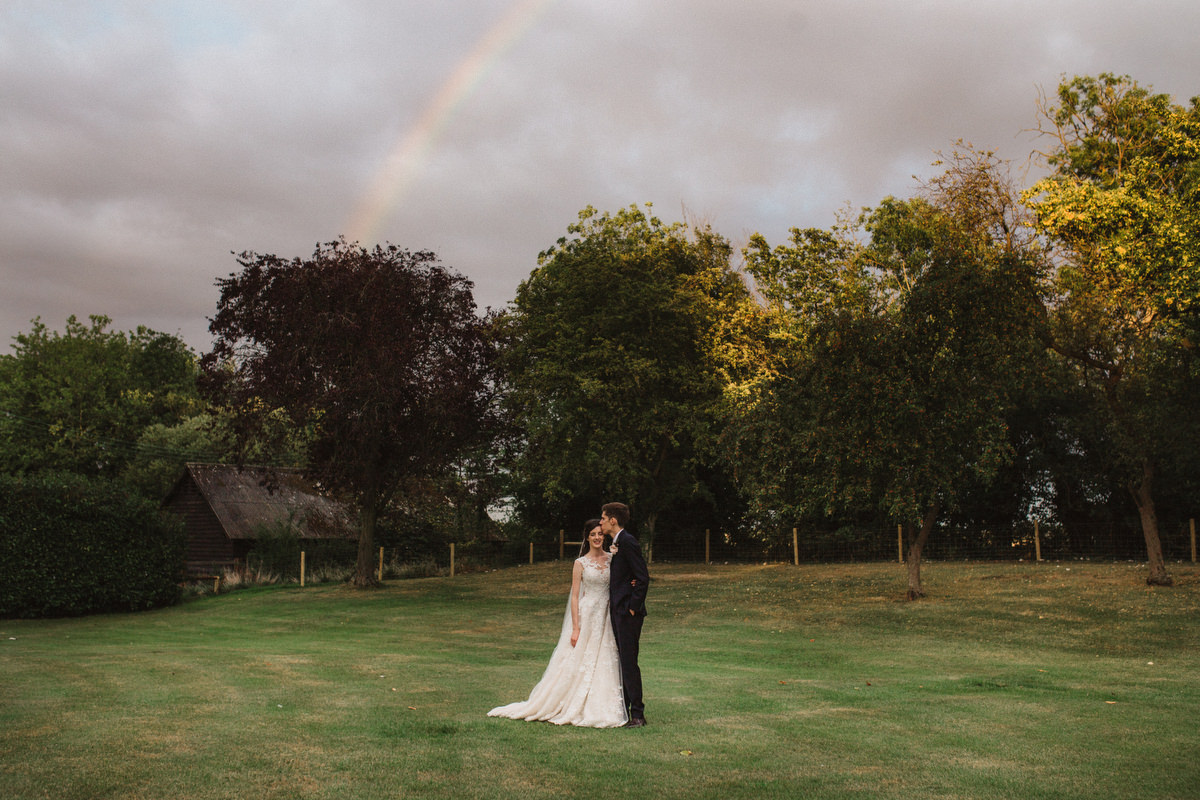 bride and groom under a rainbow outside at HAUGHLEY PARK BARN WEDDING PHOTOGRAPHY