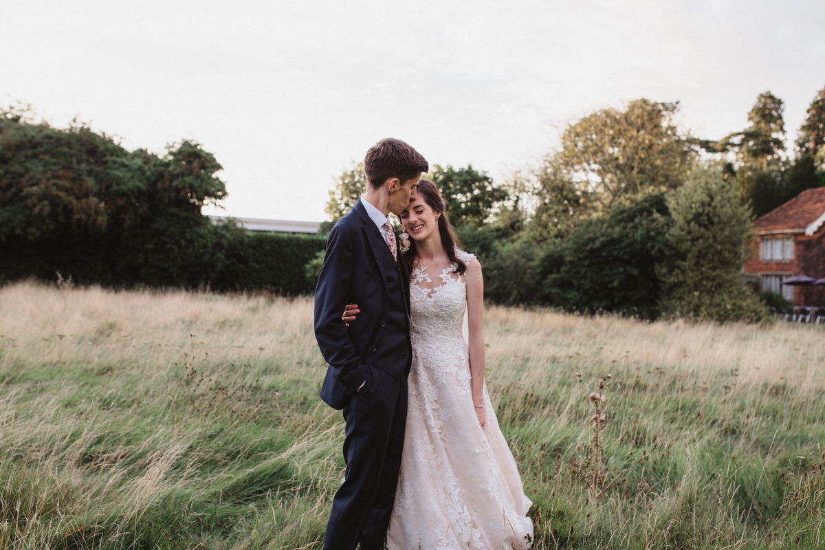 a tender moment between bride and groom in a field at HAUGHLEY PARK BARN WEDDING PHOTOGRAPHY