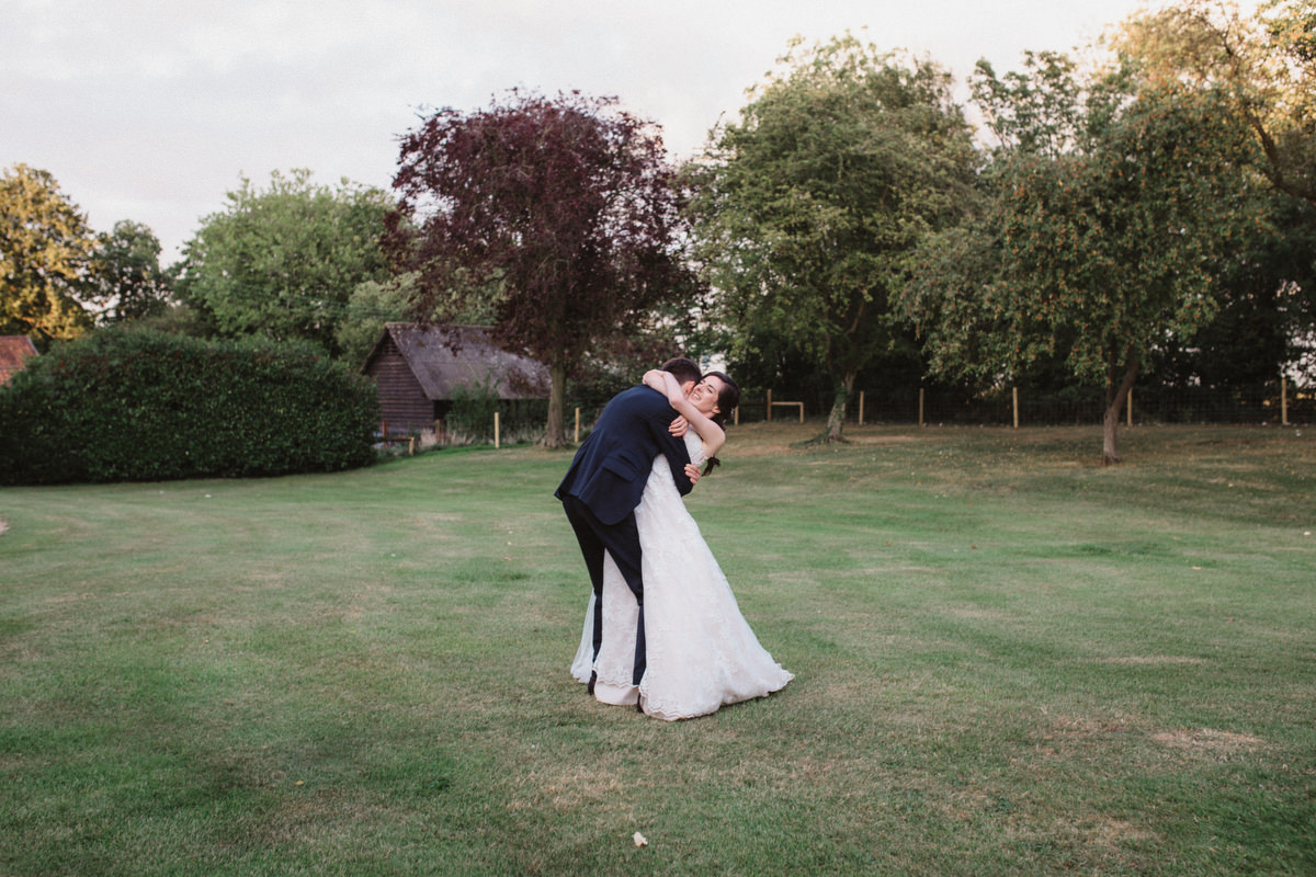 groom picking up bride at HAUGHLEY PARK BARN WEDDING PHOTOGRAPHY