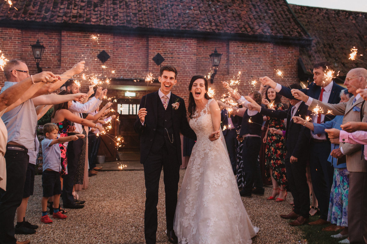 bride and groom laughing down sparkler line outside HAUGHLEY PARK BARN WEDDING PHOTOGRAPHY