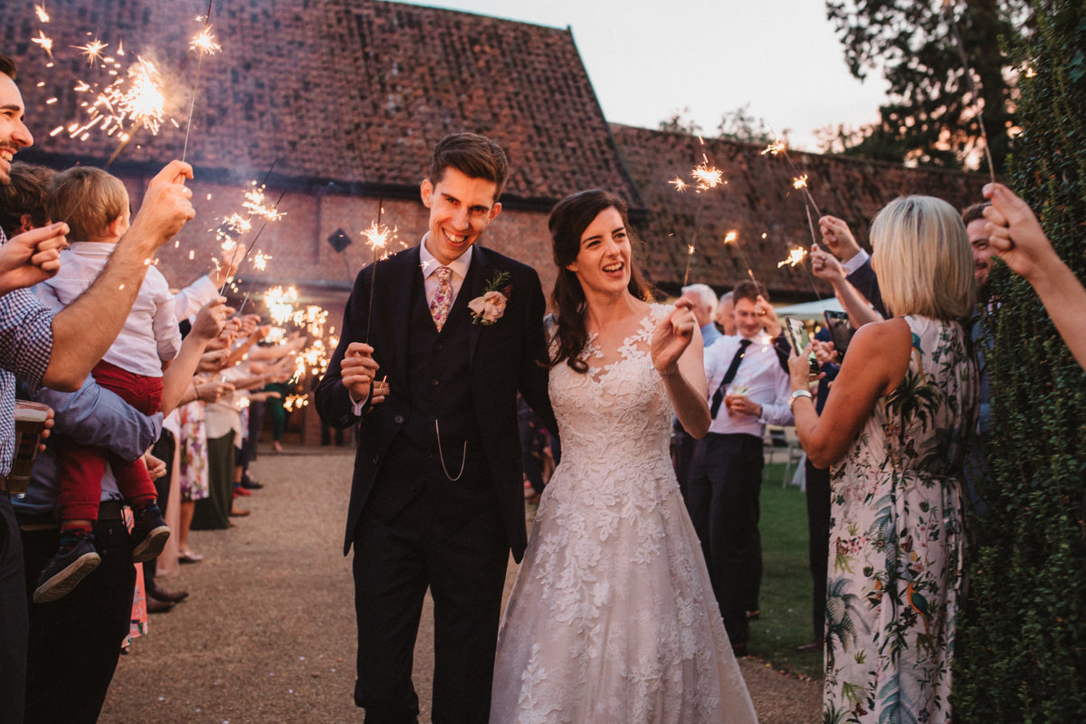 bride and groom with sparklers outside HAUGHLEY PARK BARN WEDDING PHOTOGRAPHY